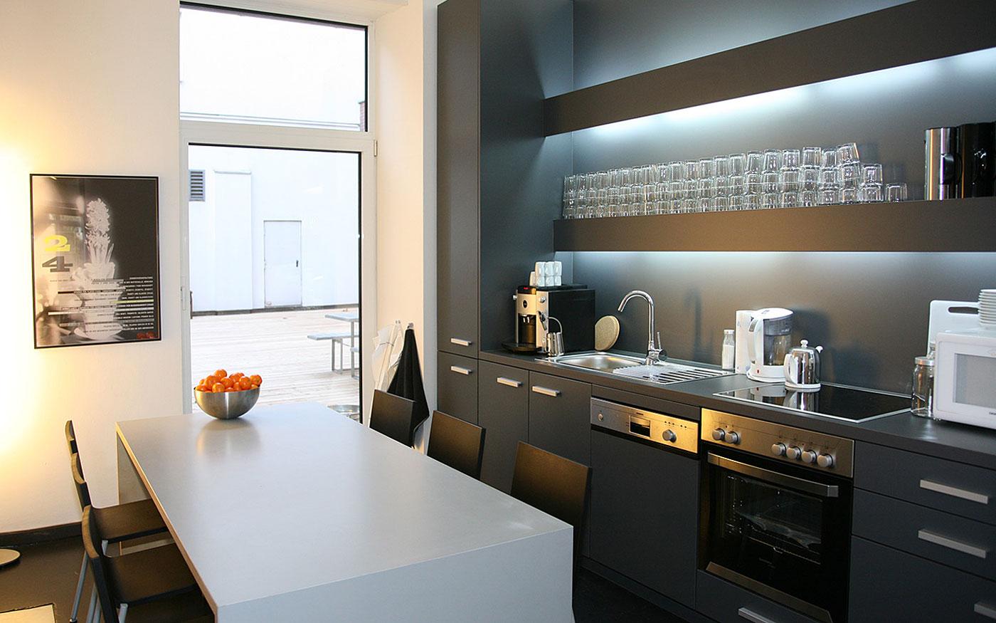 Moderne dunkle Küche und heller Esstisch